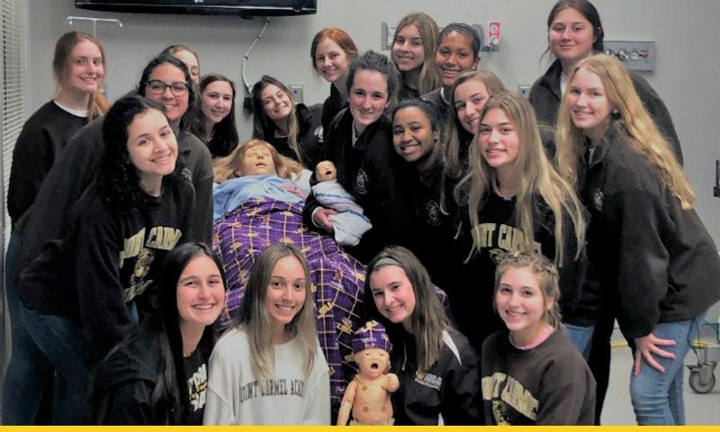 High school nursing students grouped around patient mannequin