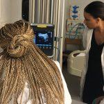 Three nursing students looking at a vital signs monitor.