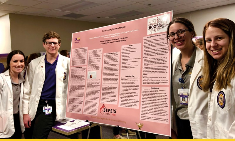 Nursing students posing by their poster presentations.