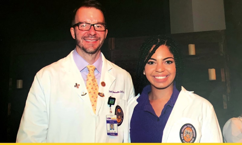 A female nursing student, Morgan Bourgeois, wearing her white coat and standing next to Todd Tartavoulle, Program Director for Traditional BSN Program and Associate Professor of Clinical Nursing.