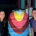 Two female nursing students with a brightly painted rain barrel.