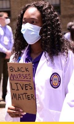 Image of a cardboard sign that reads black nurses lives matter held up to the LSU School of Nursing building sign.