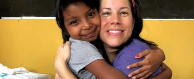 A woman and child hugging.