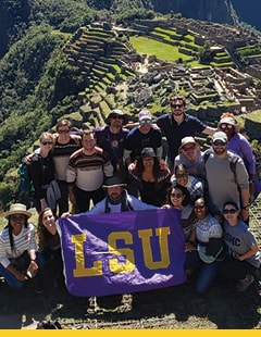 LSU School of Nursing students carrying an LSU banner, with the backdrop of Machu Picchu ruins in Peru.