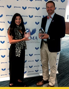 Jessica Landry and Todd Tartavoulle holding their achievement awards.