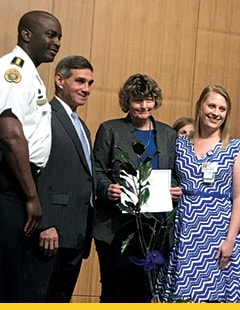 Randy Rosamond holding her award and standing with three others from the New Orleans Children's Advocacy Center.