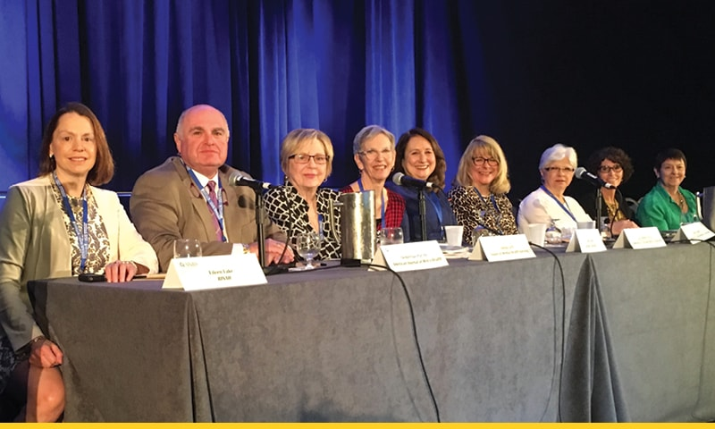 Nine people doing a presentation. A sign that reads Southern Nursing Research Society is displayed on a podium near the group. Dr. Demetrius Porche is second from left in front of a microphone.