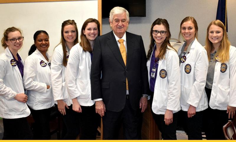Louisiana Senate President John Alario posing with seven LSU Health New Orleans School of Nursing students.