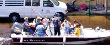 Nurses and other health care professionals in a motorboat navigating a flooded New Orleans street after Hurricane Katrina.