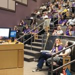 Faculty member Kendra Barrier presenting a lecture to a theater full of nursing students.