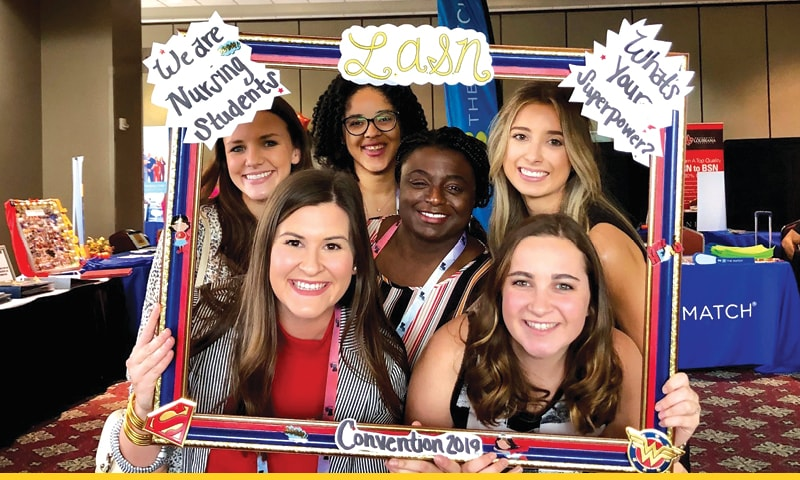 Six School of Nursing students posing in a photo frame during the LASN annual convention.