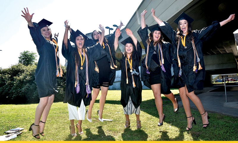 Group of graduates in caps and gowns waving their hands