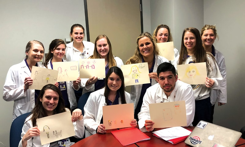 11 LSU School of Nursing students showing their illustrations of their experiences in their population health courses.