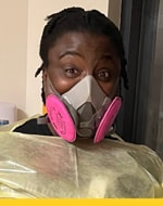 Zoe is pictured in yellow scrubs wearing a pink respirator.