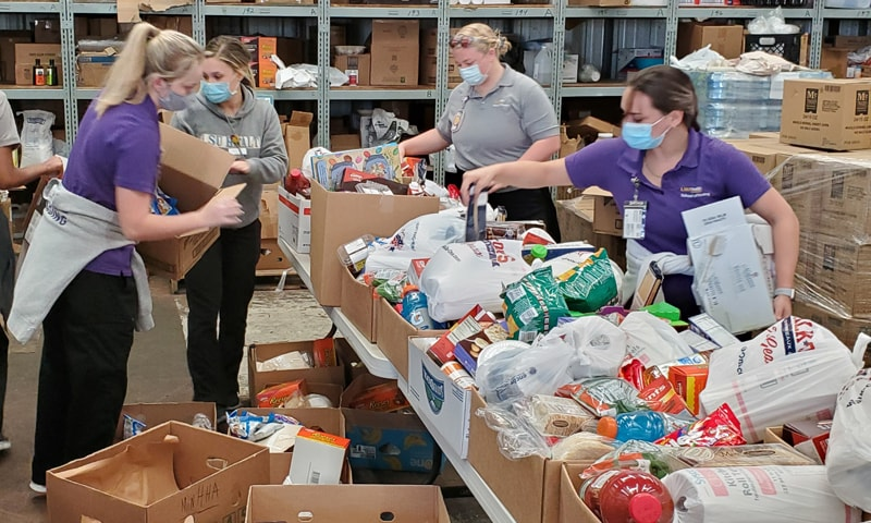 Four LSU Health New Orleans School of Nursing students in masks sorting food donations for the Giving Hope Food Bank.