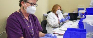 Two vaccination clinic staff members, one in purple scrubs and one in a lab coat, prepare Pfizer vaccine doses.