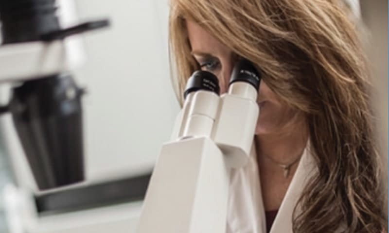 Dr. Marcy Purnell is pictured looking through a microscope.