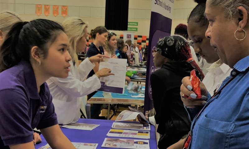 A School of Nursing student in a purple shirt offers recruitment paperwork to a high school student and the woman accompanying her.